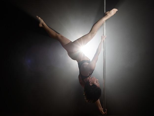 Bella ragazza esile con pilone. danzatrice del palo femminile