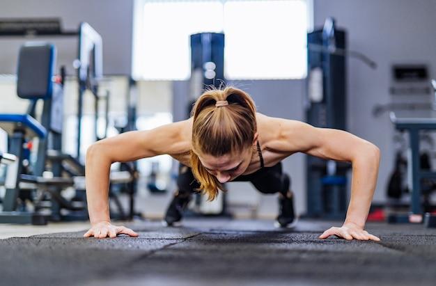 Bella ragazza fa flessioni dal pavimento per allenare i muscoli delle mani in palestra
