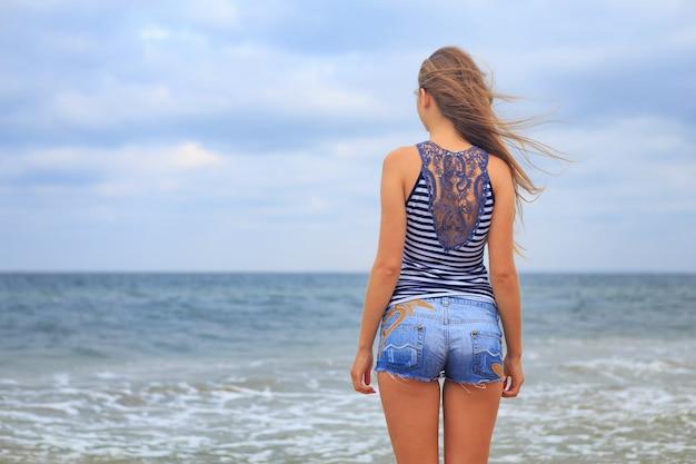 Bella ragazza felice che cammina sulla spiaggia in una maglietta a strisce e shorts in denim, capelli svolazzanti nel vento