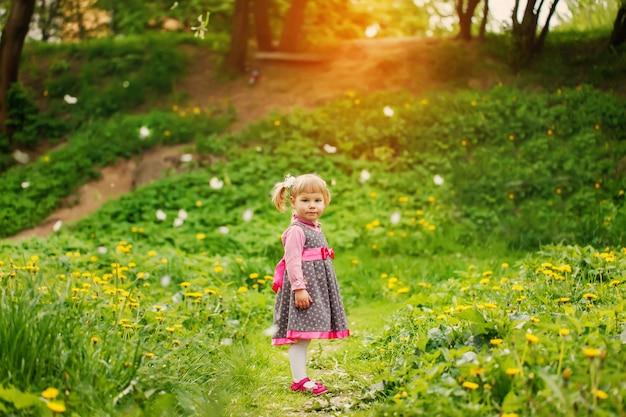 Bella ragazza felice che gioca in un campo di fiori gialli in una sera di primavera soleggiata