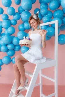 Bella ragazza felice che tiene la torta di compleanno con candele e 20 numeri.