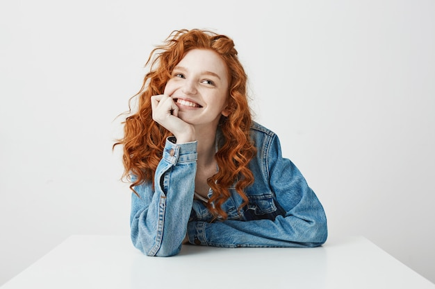 Bella ragazza felice con capelli ricci e le lentiggini che sogna sorridente che si siede alla tavola.