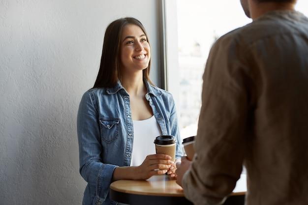 Bella ragazza felice con i capelli scuri in maglietta bianca sotto la camicia di jeans, beve caffè e sorride, ascoltando la storia di un amico della festa di ieri.