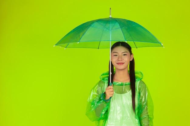 Bella ragazza felice, con indosso abiti verdi, ombrello e cappotto, giornata di pioggia.