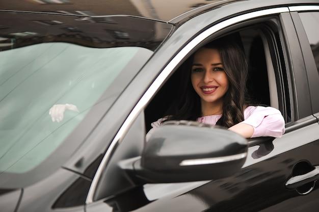 Bella ragazza felice del brunette sulla finestra di automobile