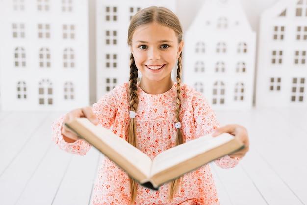 Bella ragazza felice in posa con un libro