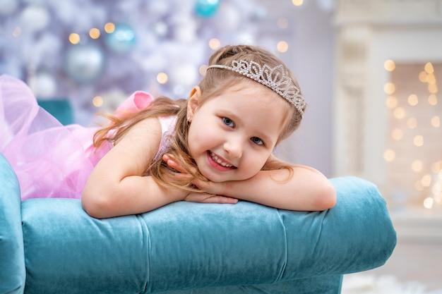 Bella ragazza felice in un bel vestito si trova sul divano