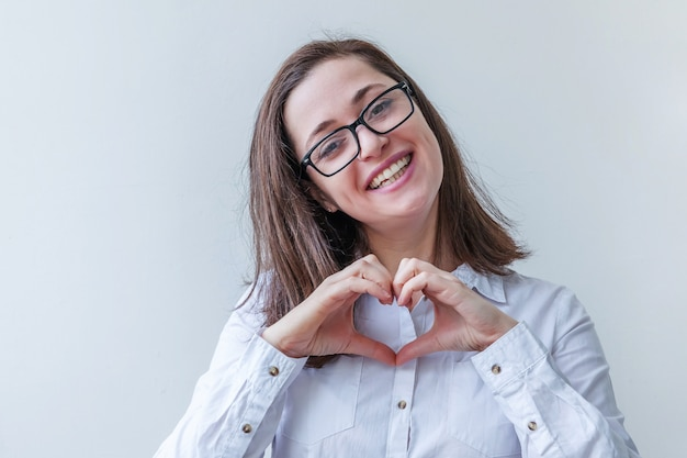 Bella ragazza felice sorridente. giovane donna semplice del ritratto di bellezza in occhiali che mostrano il segno del cuore con le mani isolate su bianco. emozioni umane positive espressione facciale linguaggio del corpo.