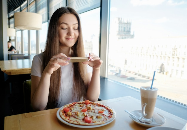 Bella ragazza felice sta facendo foto di cibo nella caffetteria, latte sul tavolo pizza, comunicazione nei social network