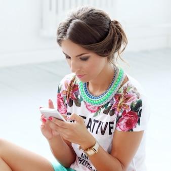 Bella ragazza guarda il telefono