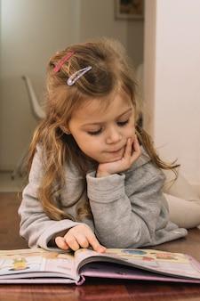 Bella ragazza guardando le immagini nel libro