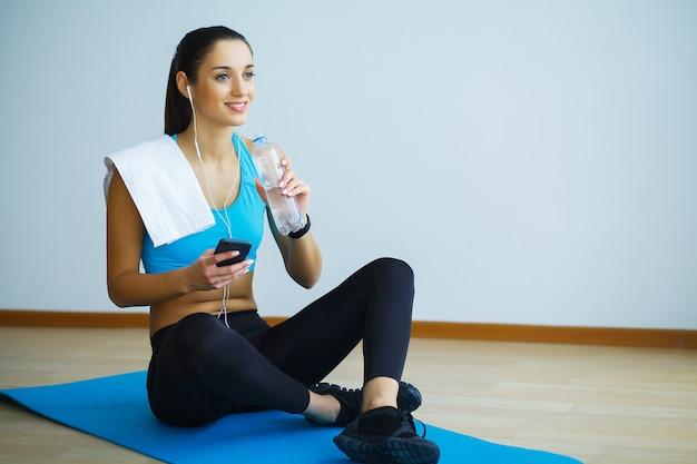 Bella ragazza in abiti sportivi con bottiglia d'acqua