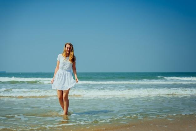 Bella ragazza in abito bianco divertiti e rilassati sulla spiaggia. viaggi e vacanze.