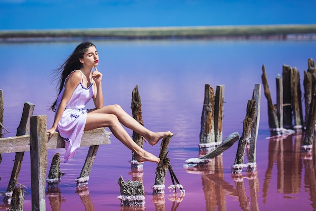 Bella ragazza in abito bianco lungo in posa sul lago rosa salato.