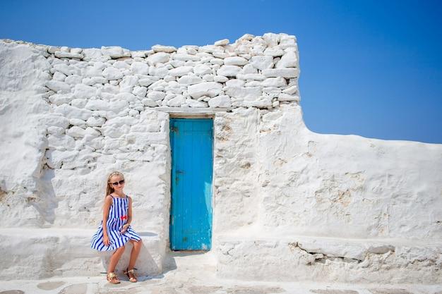 Bella ragazza in abito blu divertirsi all'aperto vicino alla chiesa di paraportiani.