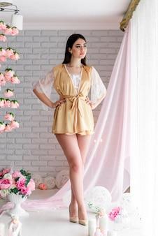 Bella ragazza in abito boudoir di pizzo bianco sui colori di sfondo arredamento con grande finestra