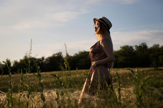 Bella ragazza in abito e cappello sul campo al tramonto.