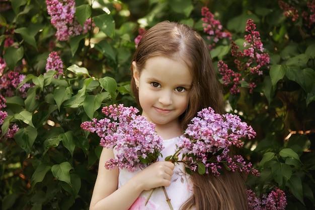 Bella ragazza in abito in posa vicino a bush di lillà
