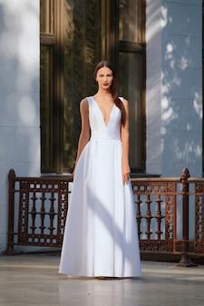 Bella ragazza in abito lungo bianco con scollo profondo. modello di moda che posa sul terrazzo di un palazzo.