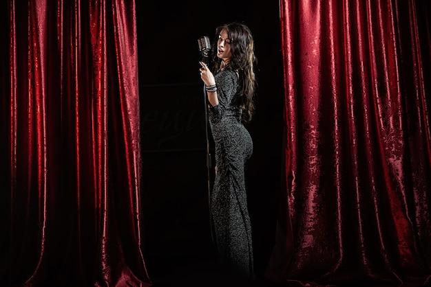 Bella ragazza in abito nero, cantando nel microfono nella sala da concerto