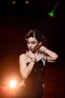 Bella ragazza in abito nero che balla sul palco.