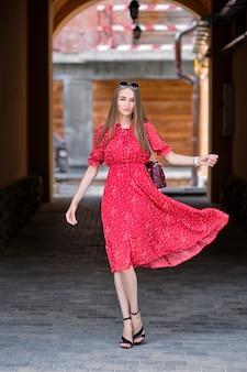 Bella ragazza in arco con vestito soffiato nel vento