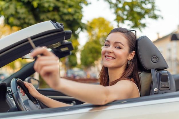 Bella ragazza in auto cabrio convertibile in una giornata di sole in una città