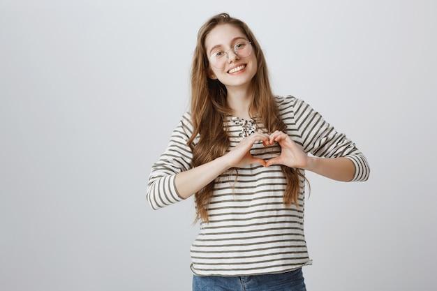 Bella ragazza in bicchieri che mostra il gesto del cuore e sorridente
