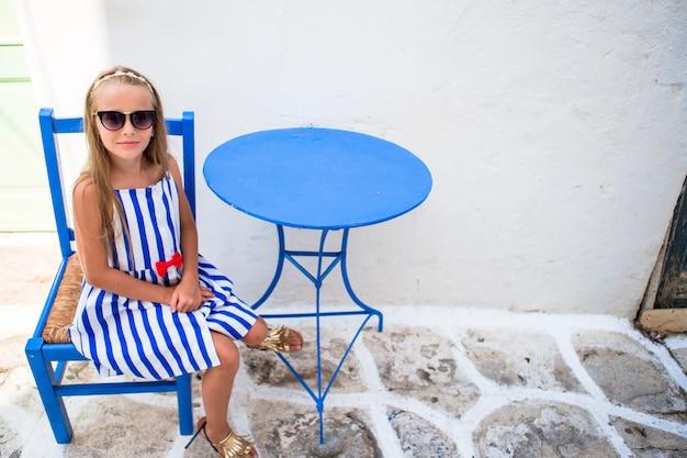 Bella ragazza in caffè all'aperto sulla strada del tipico villaggio greco sull'isola di mykonos, in grecia