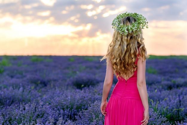 Bella ragazza in campo di lavanda al tramonto. stile grazioso della provenza della donna in una corona dei fiori e del vestito