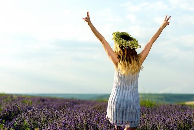 Bella ragazza in campo di lavanda. pretty woman in stile provenzale in abito bianco e corona di fiori