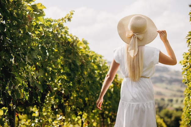 Bella ragazza in cappello che cammina sulla grande piantagione della vigna, toscana, italia.