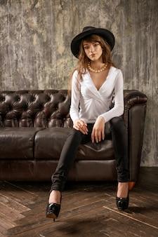 Bella ragazza in cappello nero seduto sul divano, elegante donna