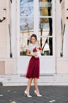 Bella ragazza in gonna in tulle marsala con acconciatura leggera che cammina sulla strada. tiene i fiori e sorride a lato