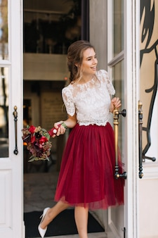 Bella ragazza in gonna in tulle marsala sulla strada. tiene i fiori e sorride a lato
