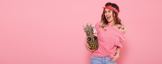 Bella ragazza in maglietta rosa, sorridente con ananas sulla parete rosa