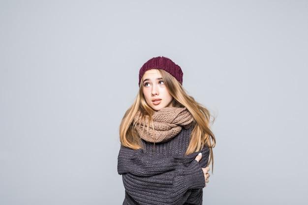 Bella ragazza in maglione grigio è freddo cercando di riscaldarsi sul grigio