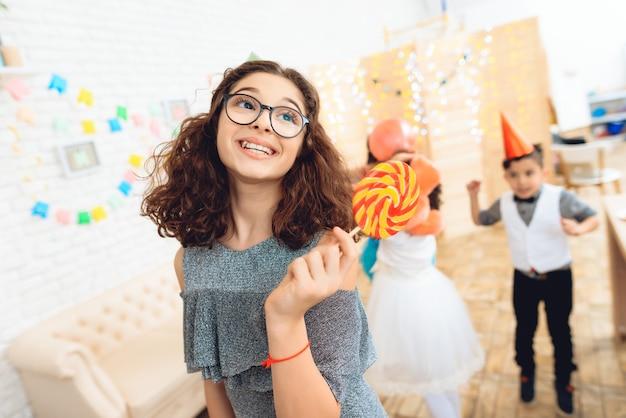 Bella ragazza in occhiali con lecca-lecca colorata