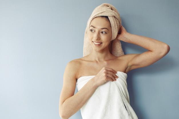 Bella ragazza in piedi in un asciugamano