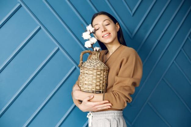Bella ragazza in piedi in uno studio con fiori di cotone