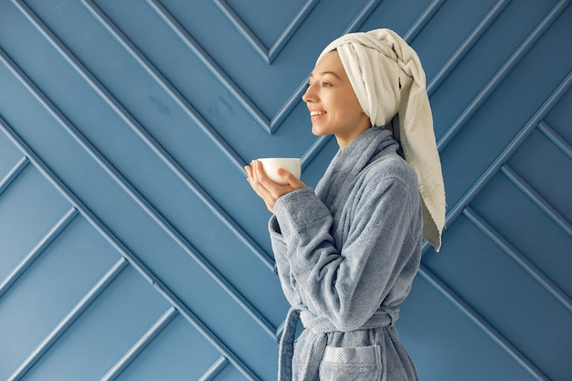 Bella ragazza in piedi in uno studio in un accappatoio blu