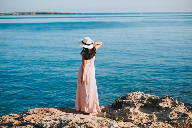 Bella ragazza in piedi sulla costa rocciosa affioramenti
