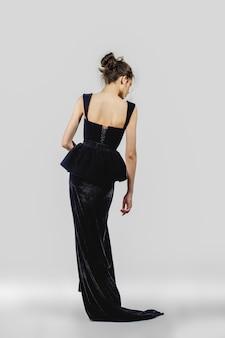 Bella ragazza in posa in abito da sera. ritratto integrale del modello di moda.