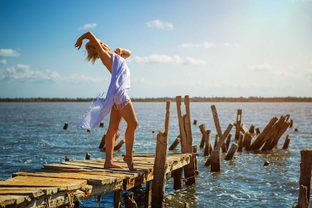 Bella ragazza in posa sul molo in una giornata di sole estivo