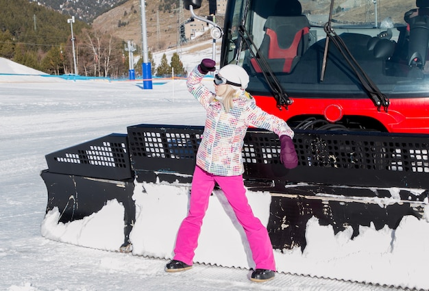 Bella ragazza in posa vicino a spazzaneve in montagna sulla neve