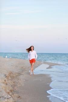 Bella ragazza in riva al mare, indossa pantaloncini e t-shirt.