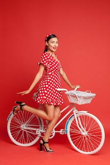 Bella ragazza in stile pin-up con una bicicletta