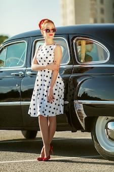 Bella ragazza in stile retrò e un'auto d'epoca