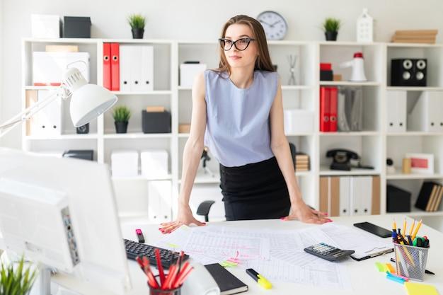 Bella ragazza in ufficio è in piedi vicino al tavolo e ci mette le mani sopra.