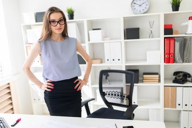 Bella ragazza in ufficio è in piedi vicino al tavolo e mise le mani sui fianchi.